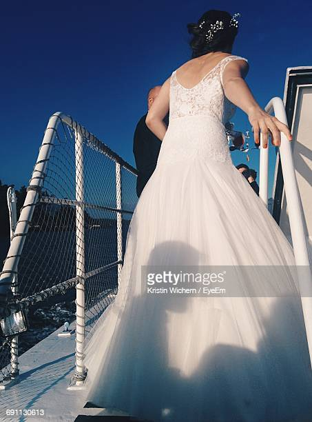 Rear View Of Bride Amidst Railing On Boat Against Clear Blue Sky