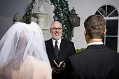 Rear view of bride and groom in front of priest in a chapel