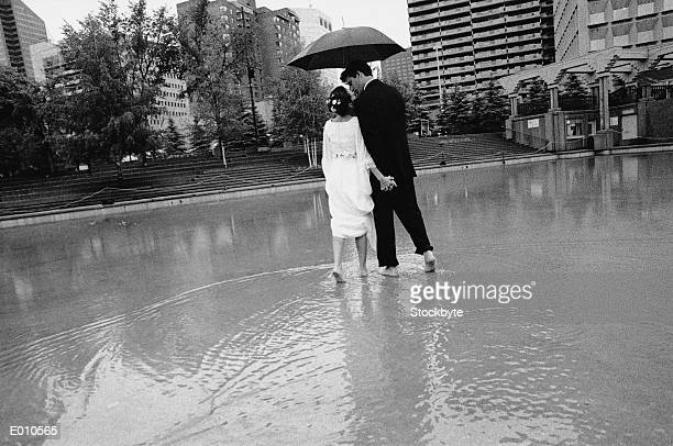 Rear view of bride & groom walking in water, under umbrella