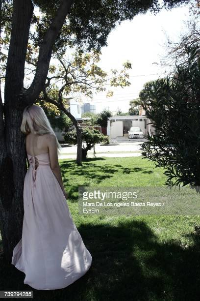 Rear View Of Bride Leaning On Tree While Standing Outdoors