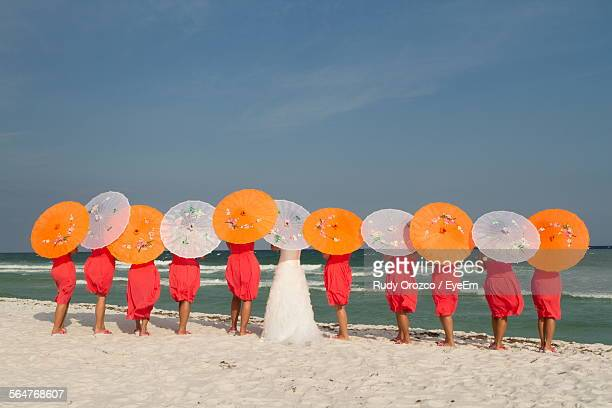 Rear View Of Bride With Her Friends Standing On Beach