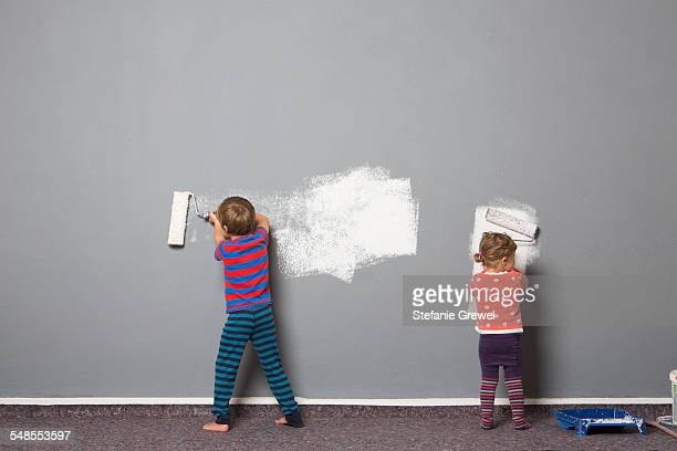 Rear view of brother and toddler sister painting wall