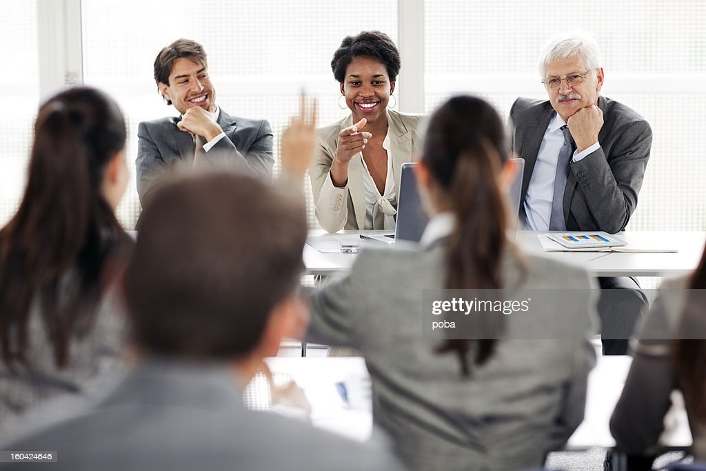 Rear view of business people attending seminar and raising  hand : Stock Photo