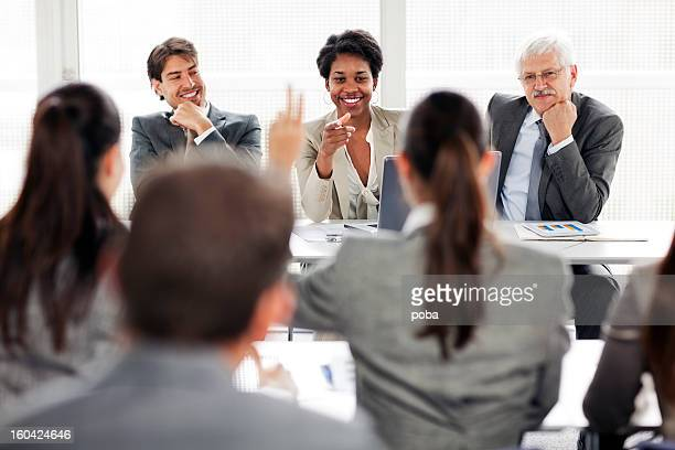 Rear view of business people attending seminar and raising  hand