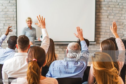 Rear view of business people with raised arms on seminar.