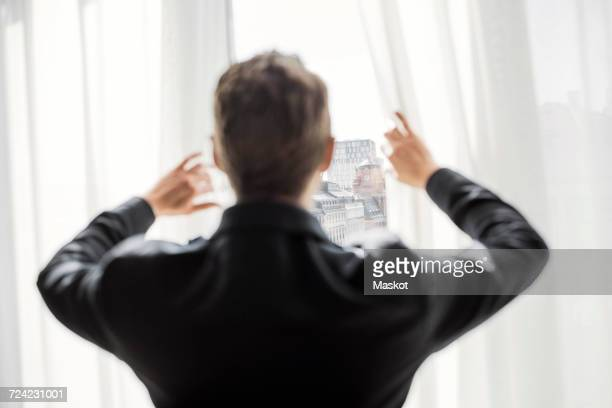 Rear view of businessman looking through hotel window