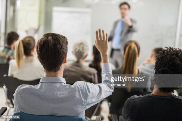 Rear view of businessman raising hand to ask a question while attending a seminar.