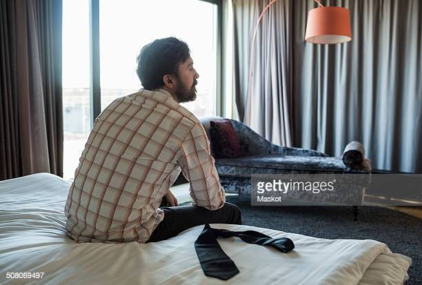 Rear view of businessman sitting on bed in hotel room