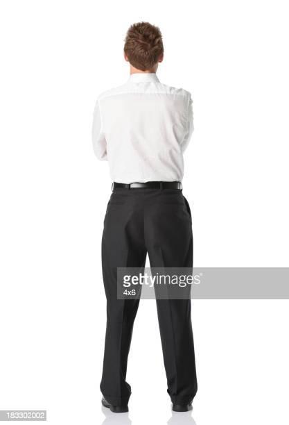 背面ビューのビジネスマン立つに腕を組む