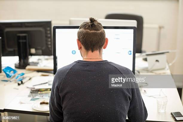 Rear view of businessman using computer in creative office