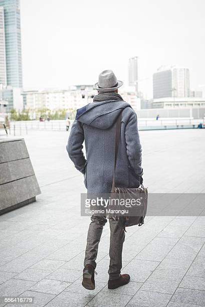 Rear view of businessman walking outside office buildings
