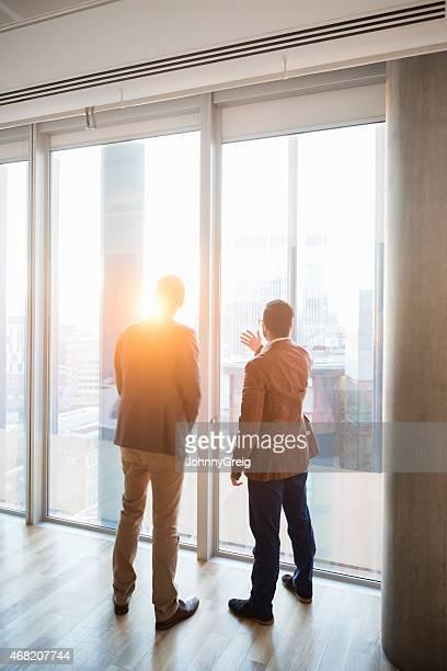 Vue arrière des hommes d'affaires en admirant la ville à travers la fenêtre