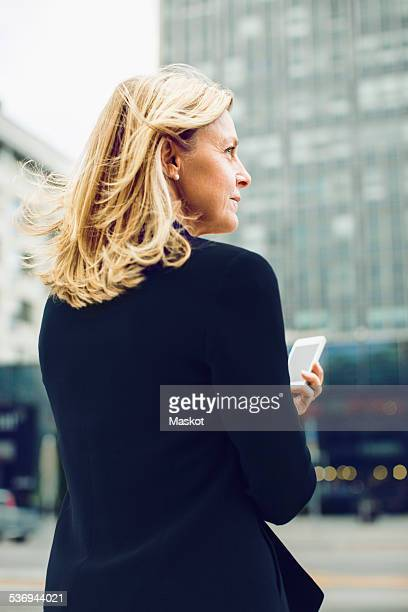 Rear view of businesswoman holding smart phone on city street