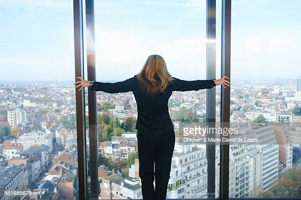 Rear view of businesswoman looking from office window at Brussels cityscape, Belgium