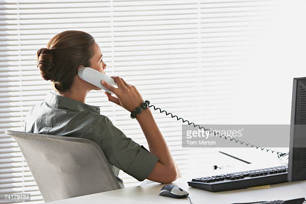 Rear view of businesswoman sitting at desk talking on telephone