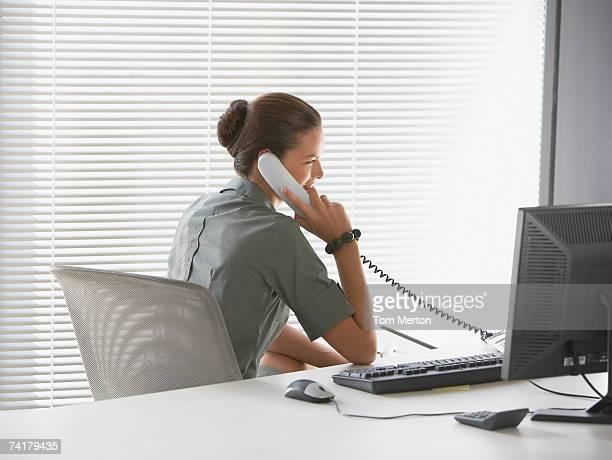 背面のビジネスウーマンのラウンジでは、デスク電話で話している