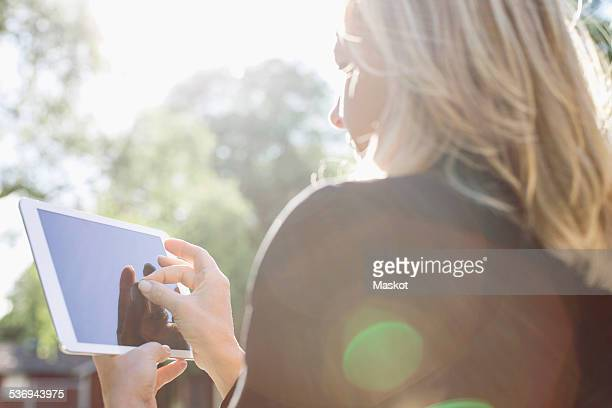 Rear view of businesswoman touching digital tablet outdoors