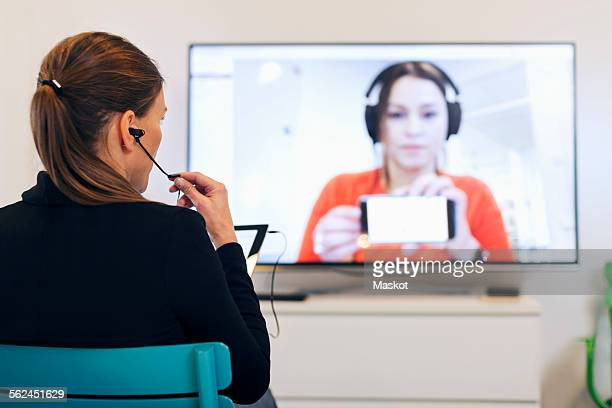 Rear view of businesswoman using in-ear headphones during conference call in creative office