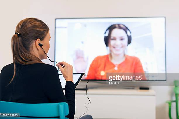Rear view of businesswoman using in-ear headphones while video conferencing in creative office