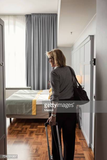 Rear view of businesswoman with luggage standing in hotel room