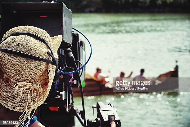 Rear View Of Cameraman Filming People On Boat