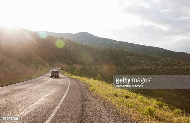 Rear view of car traveling on rural road near Torrey, Utah, USA