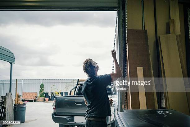 Rear view of carpenter pulling shutter at entrance of workshop