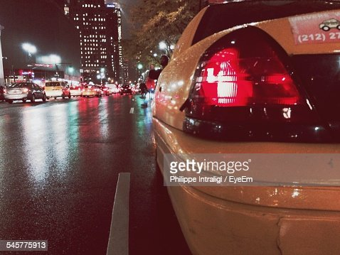 Rear View Of Cars On Road At Night