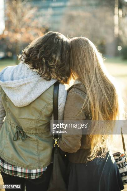 Rear view of Caucasian women hugging outdoors