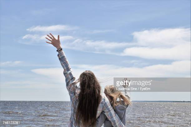 Rear View Of Cheerful Female Friends With Hand Raised Enjoying By Sea Against Sky
