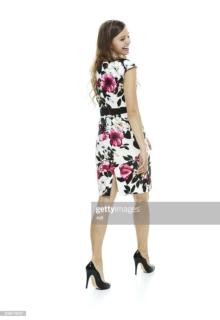 Rear view of cheerful woman in dress & walking : Stock Photo