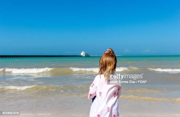 Rear view of child looking at sea