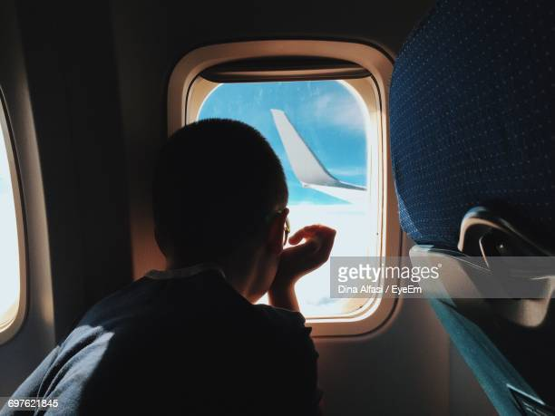 Rear View Of Child Sitting In Airplane