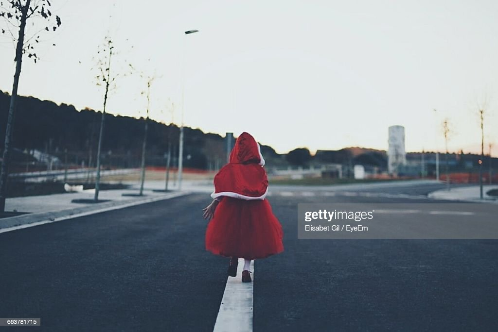 Rear View Of Child Walking On Road