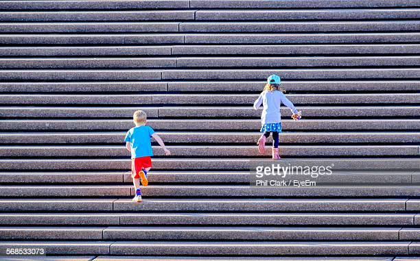 Rear View Of Children Climbing Up Steps