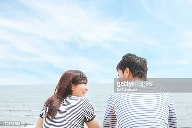 Rear view of couple at coast, face to face and laughing