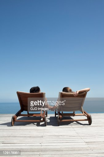 Rear view of couple holding hands while sitting on deck chairs
