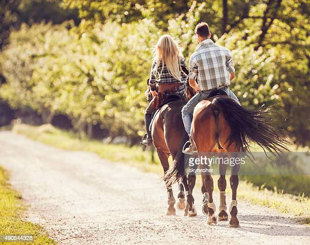 Rear view of couple horseback ridding in nature.