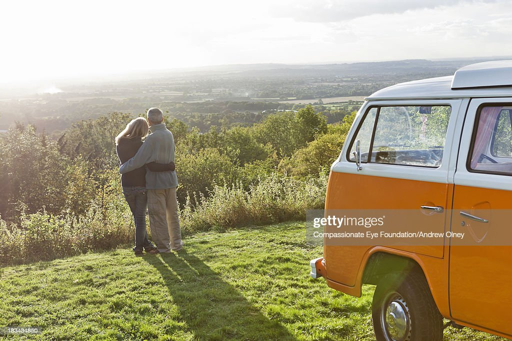 Rear view of couple hugging by camper van