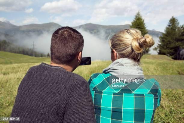 Rear view of couple in field photographing mist, Tirol, Steiermark, Austria, Europe