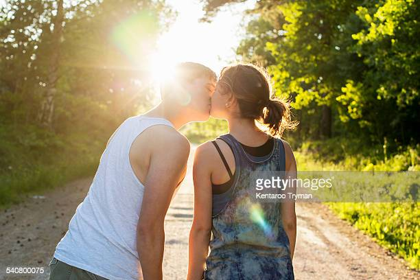 Rear view of couple kissing on dirt road against bright sun