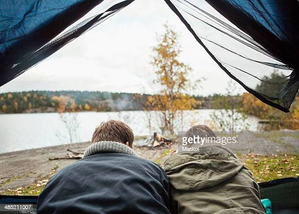 Rear view of couple lying in tent at lakeshore