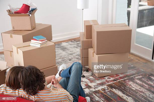 Rear view of couple on red chair in house with cardboard boxes