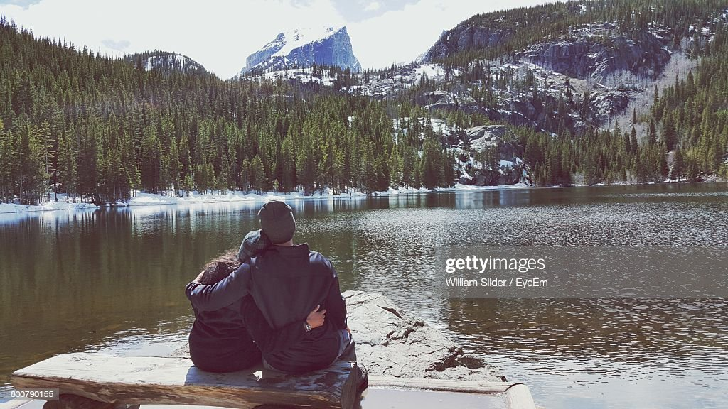 Rear View Of Couple Sitting On Bench At Bear Lakes