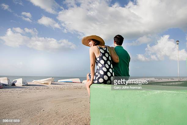 Rear view of couple sitting on wall near beach