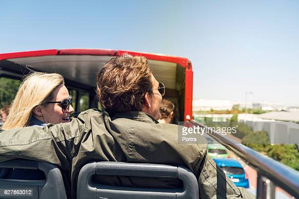 Rear view of couple traveling in open-air bus
