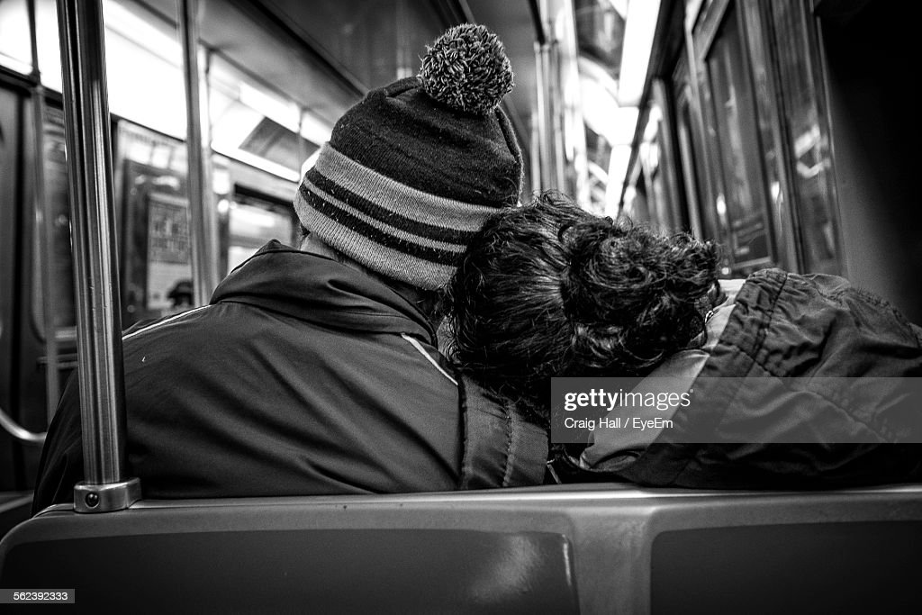 Rear View Of Couple Traveling On Subway Train : Stock Photo