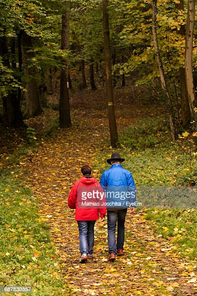 Rear View Of Couple Walking On Footpath At Forest During Winter