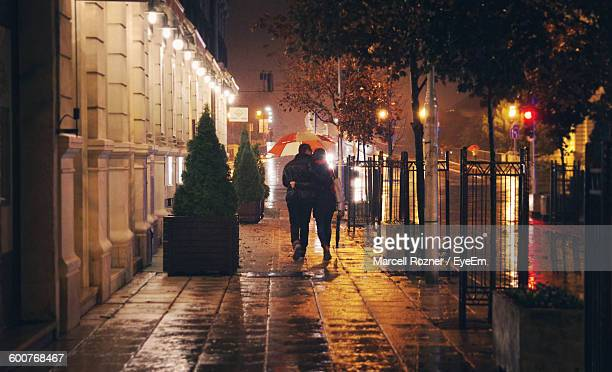 Rear View Of Couple Walking On Street During Monsoon Night