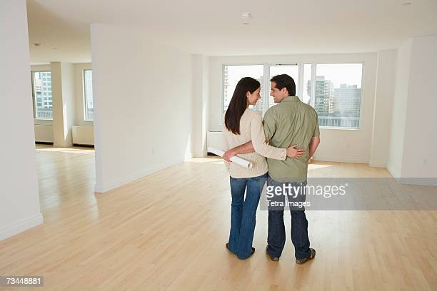 Rear view of couple with blueprints in empty house